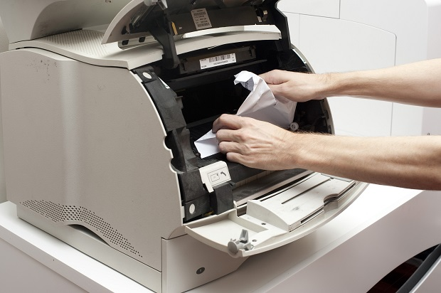 A man's hands freeing up a paper jam in an opened office printer